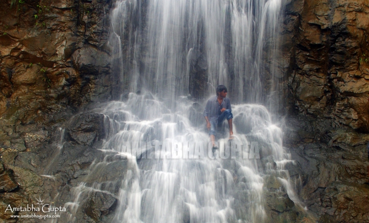 A local resident taking a bath at one of the many waterfalls at Tamhini Ghat